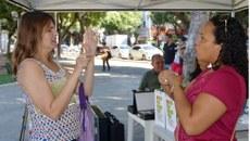 Atendimento da tradutora/intérprete de Libras do Campus, Vanessa Castro (dir.), a uma pessoa surda durante evento na Praça dos Pioneiros/GV